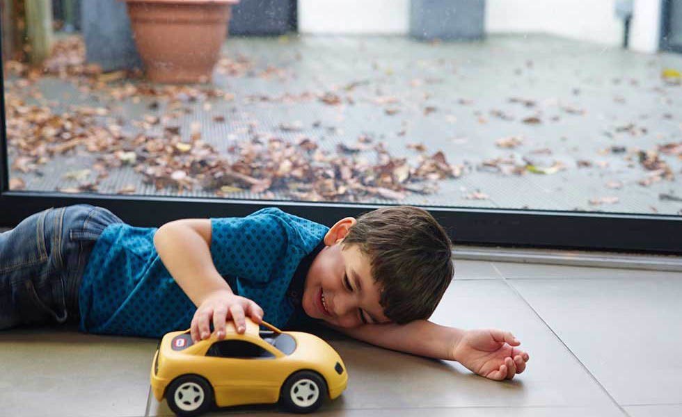 boy on tiled floor next to window playing with toy car