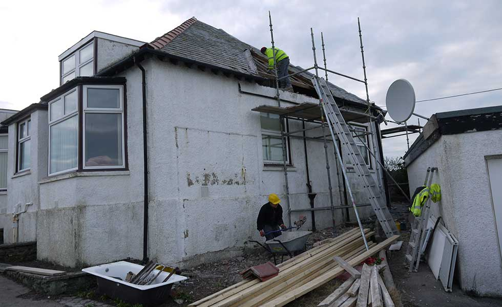 builders working on a bungalow roof in Anglesey