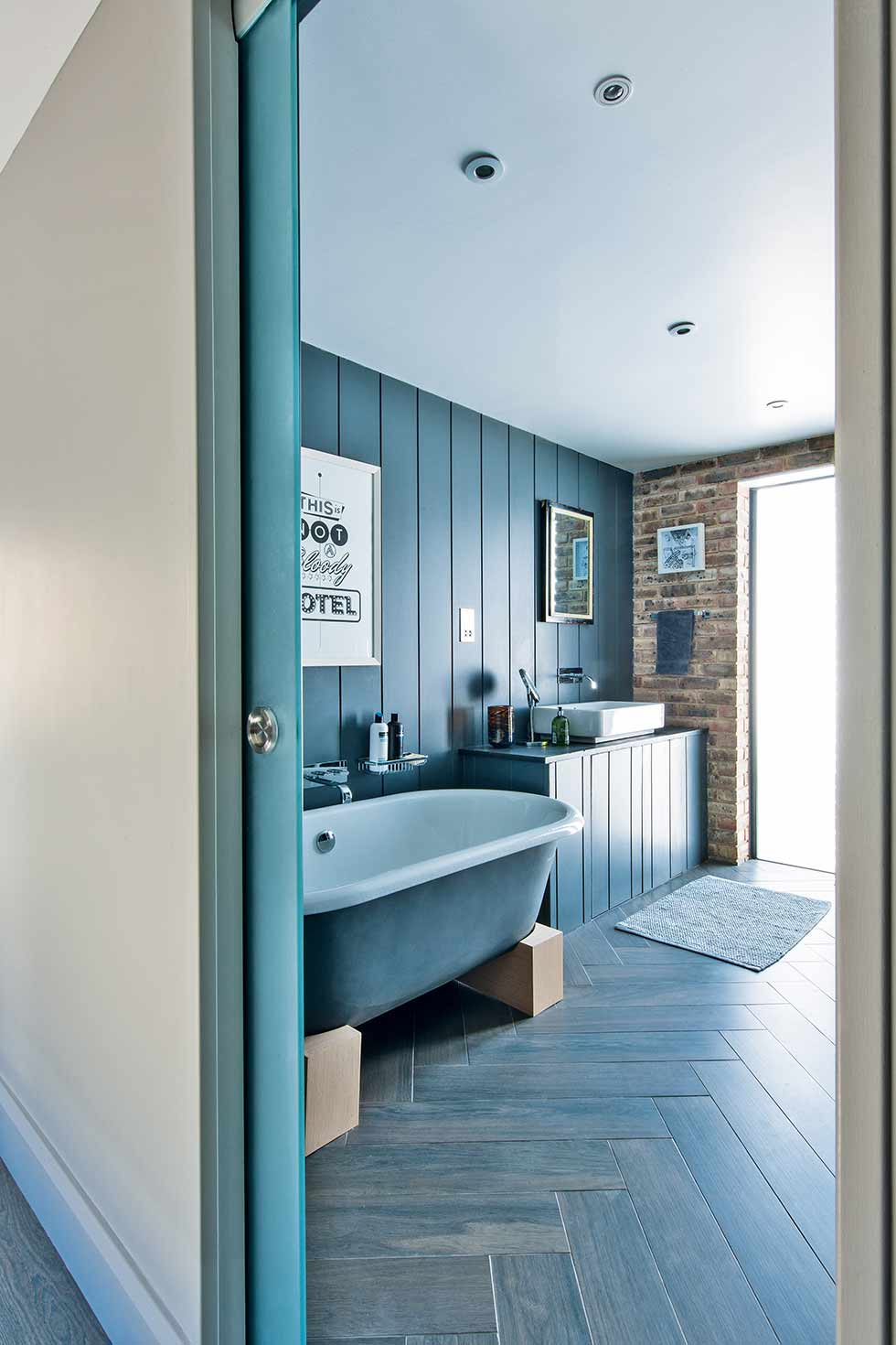 Loft style self build grey bathroom with roll top bath