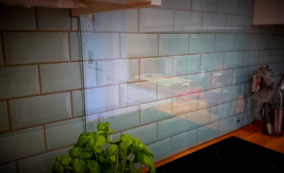 glass splash back over duck egg blue metro tiles in kitchen
