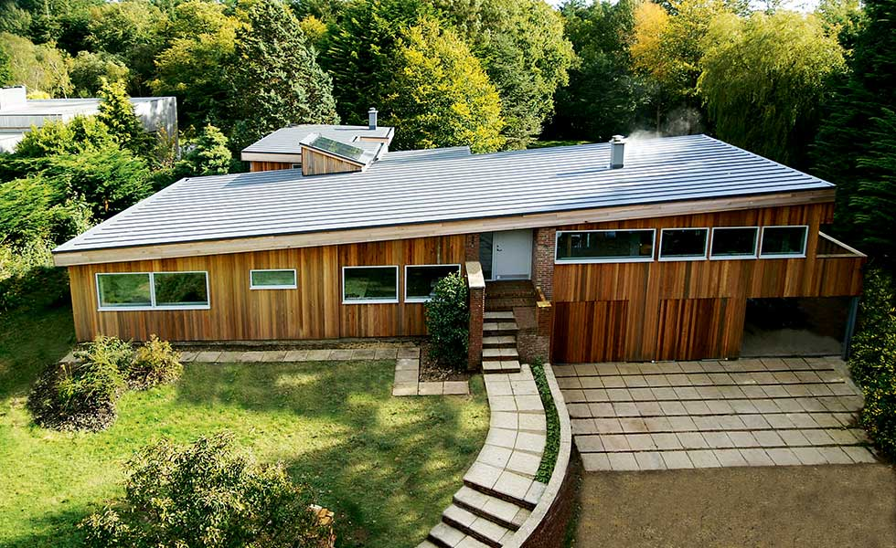 timber clad contemporary self build with a sloping roof