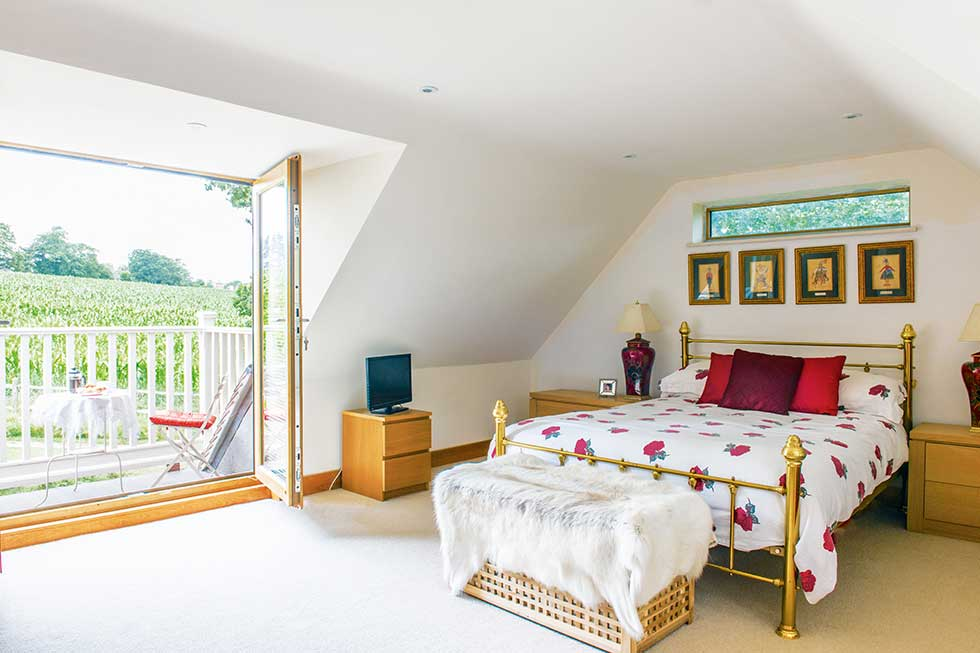 traditional style self build home master bedroom with gable balcony
