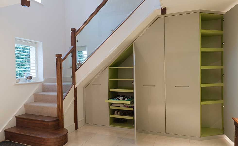 Understairs cupboards under a stair with wooden newel posts and banister and glass balustrade