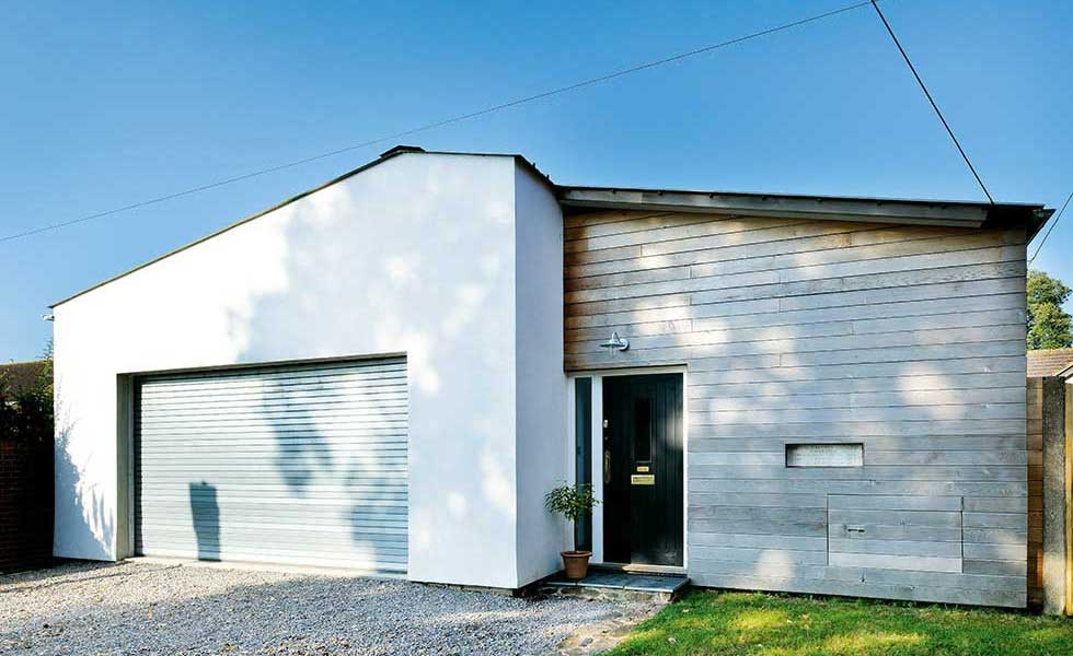 exterior of converted youth club in Devon with white render and timber cladding