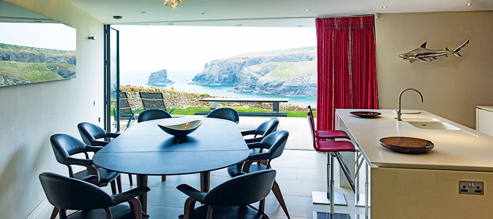 kitchen diner opening to patio of cliff top self build in Cornwall