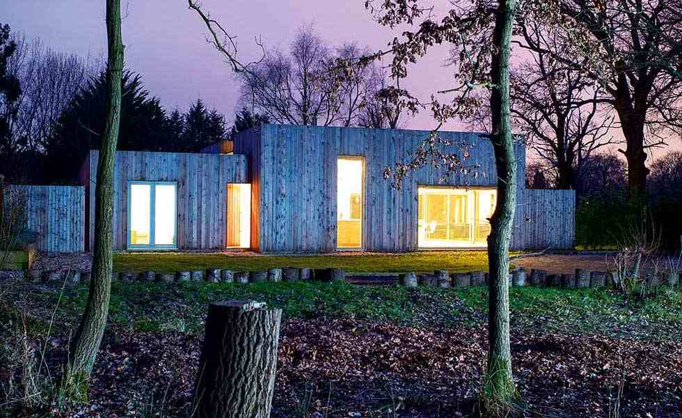 larch clad steel frame self build with lights on at dusk