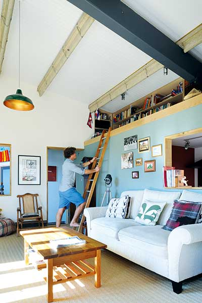 man reaching to mezzanine level with bookcases in converted youth club home