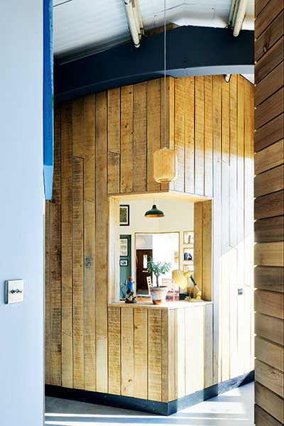 wood clad corner wall with window between living spaces