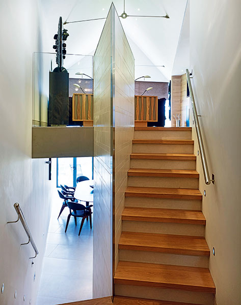 wooden staircase with vaulted stairwell