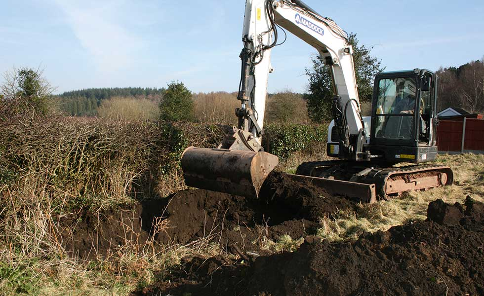 Digger removing topsoil on building site