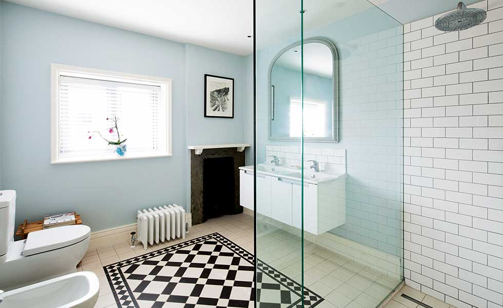 renovated blue bathroom with black and white floor tiles and walk in shower