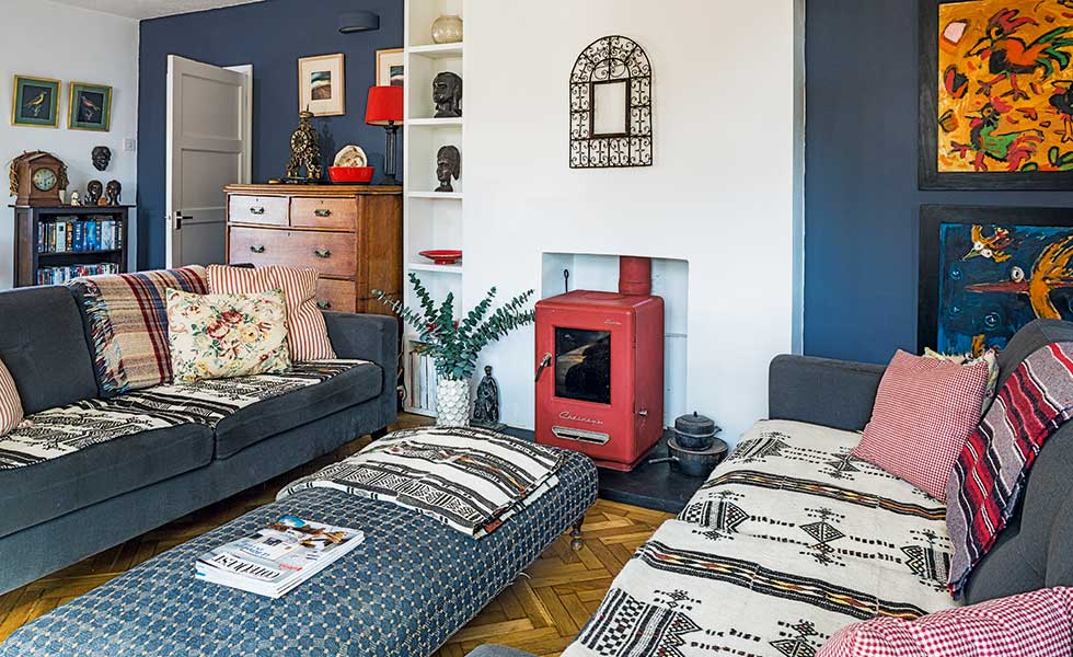 eclectic blue living room with red woodburning stove from Chesneys