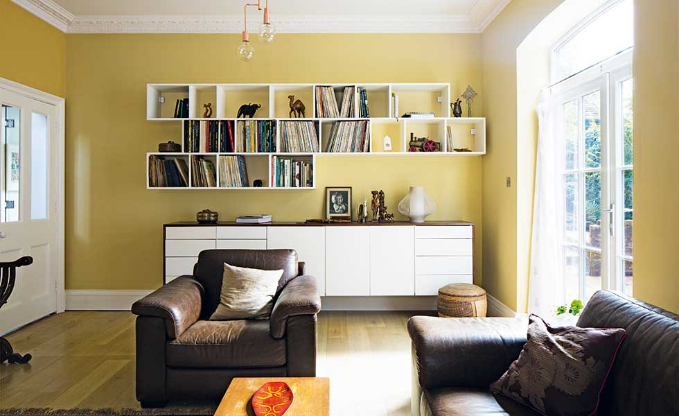 lounge with yellow walls and mounted shelving