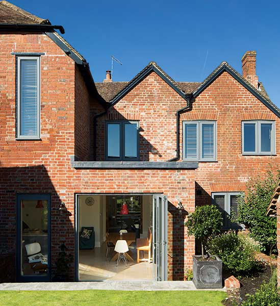 Rear elevation of a renovated period home with open bi fold doors to kitchen diner