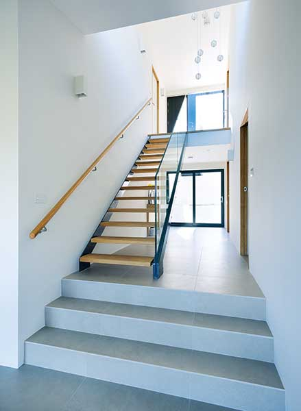stairwell with white walls and wooden stairs in split level bungalow
