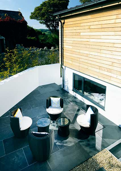 sunken terrace with seating in garden on sloping site