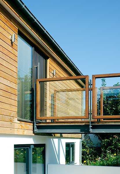 glass and wood walkway entrance to sloping site home