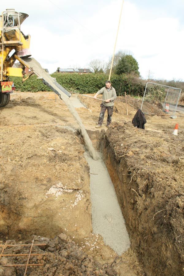 Pouring the concrete into trenches to create the foundations