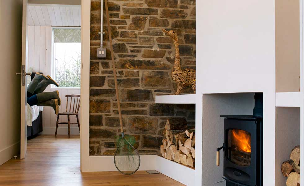 exposed brick wall in lounge space with log burner