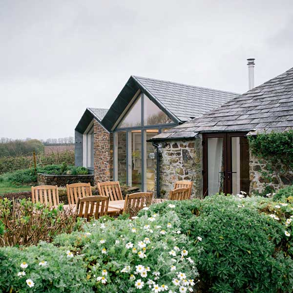 stone cottage with glass front and patio area