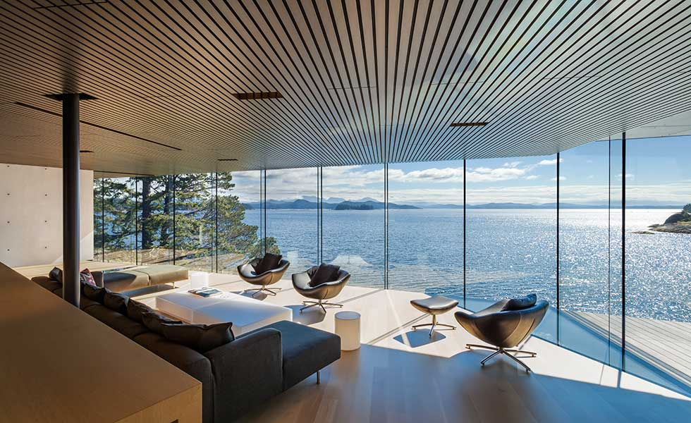living room view of modern home with glass windows overlooking lake