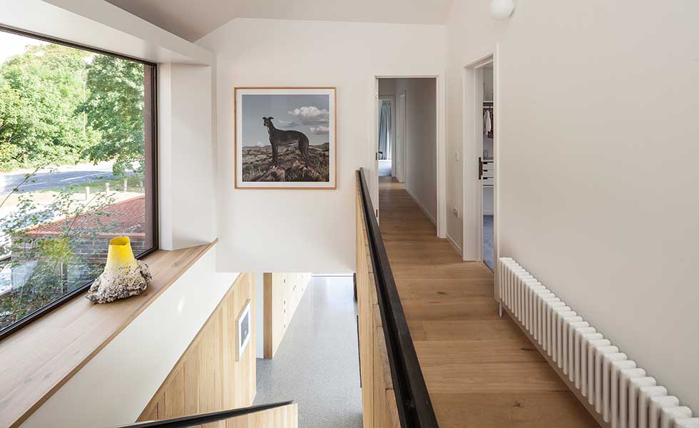 white hallway with wooden flooring and artwork of dog