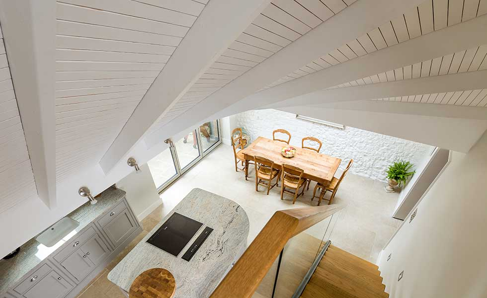 shot from above of open plan kitchen with marble topped island and wooden table