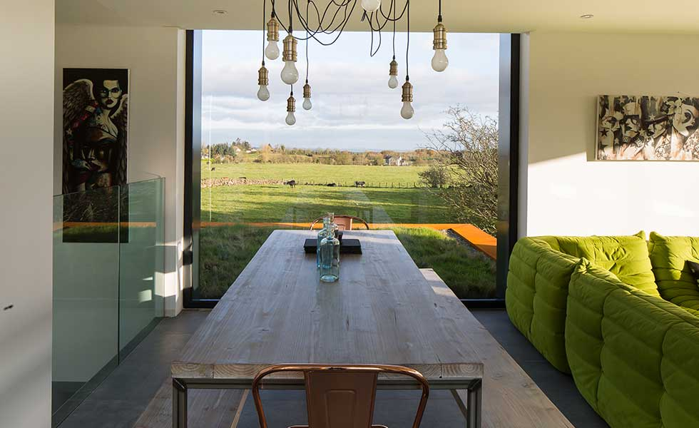 dining room with large glass window overlooking countryside, with exposed lightbulb fiixture