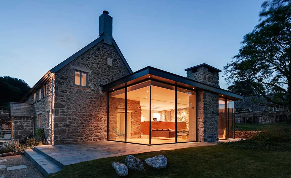 evening shot of glass extension attached to seventeenth century farmhouse