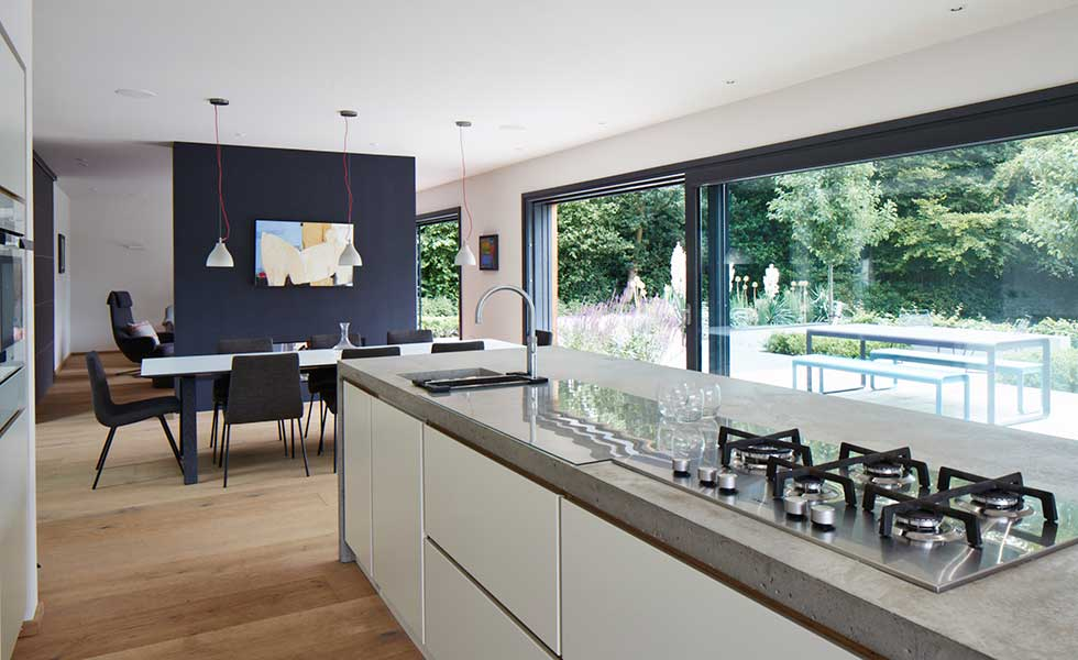 open plan living space with large glass sliding doors, wooden flooring and dark feature wall
