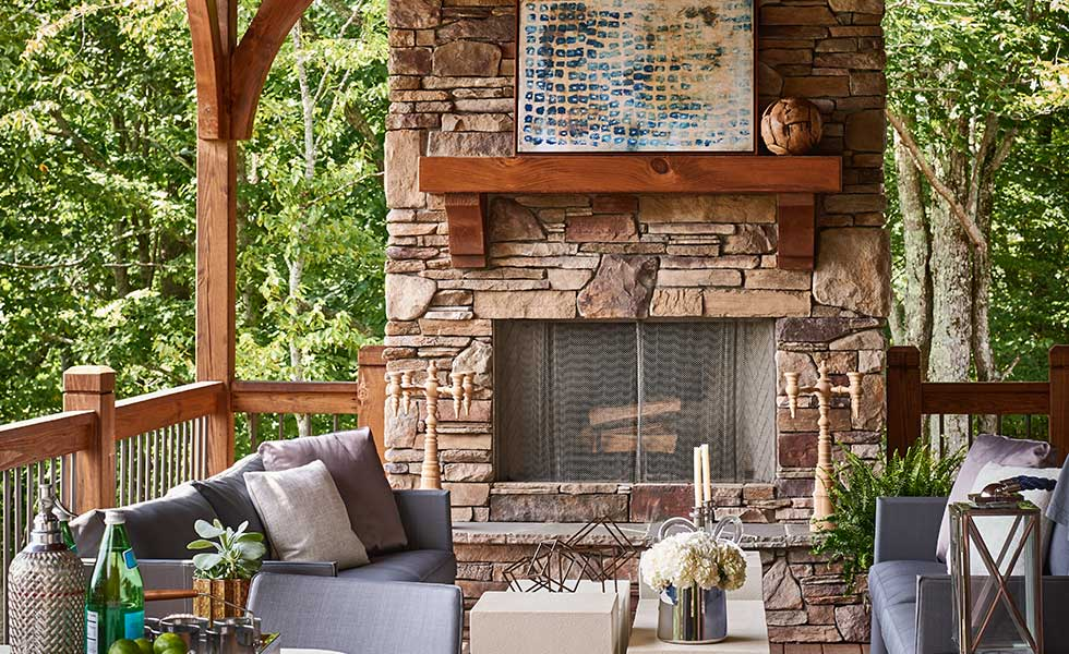 outside porch exposed brick fireplace with comfortable seating area