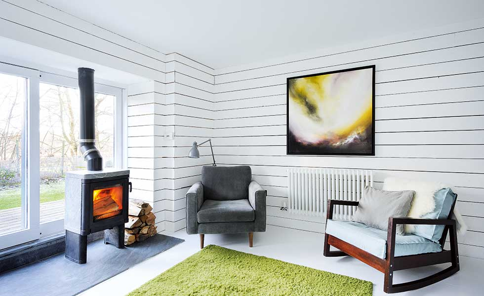 scandi style living room with white panelled walls, a green rug and small log burner