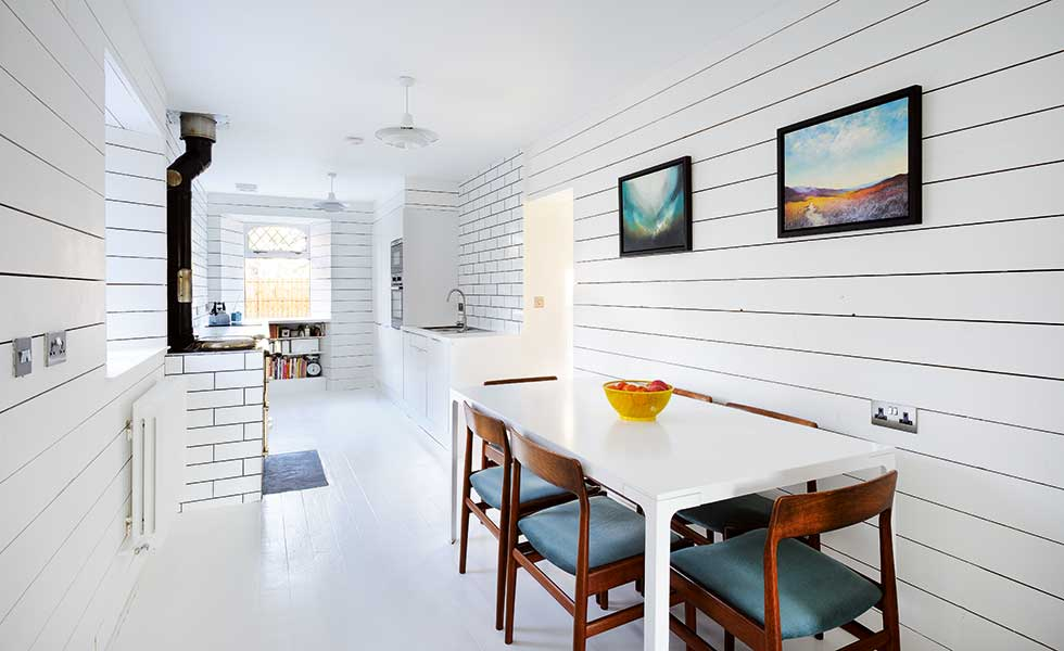 scandi style open plan room with white panelled walls, dining table and wooden chairs