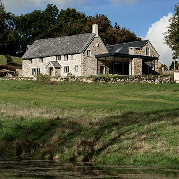 countryside shot of seventeenth century farmhouse with modern glass extension
