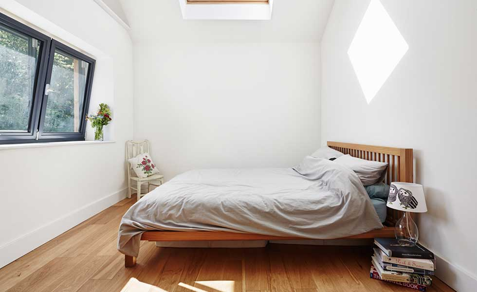 white bedroom with one large window, a wooden bed and grey bedding
