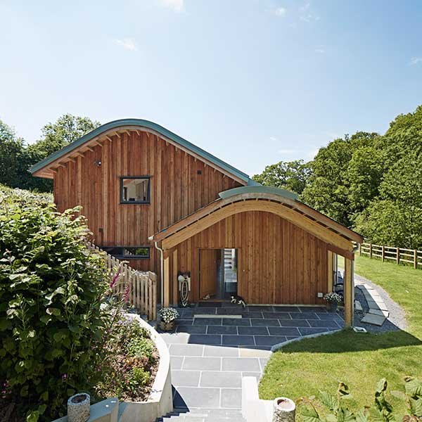 curved roof wooden panelled home in open green space