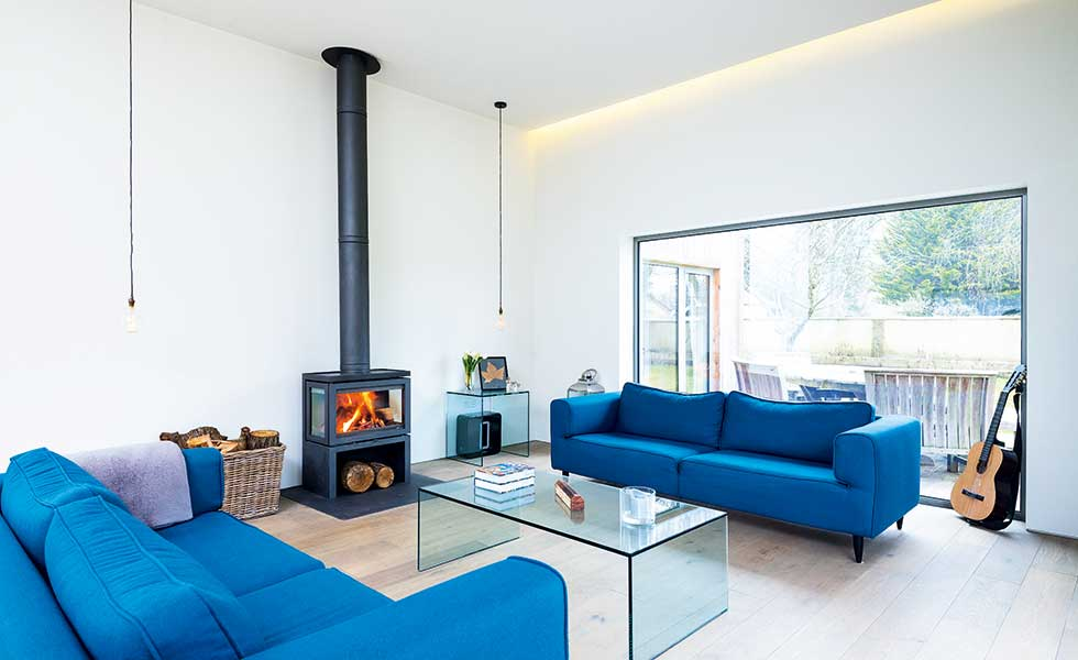 modern white living room with wood burner and blue sofas