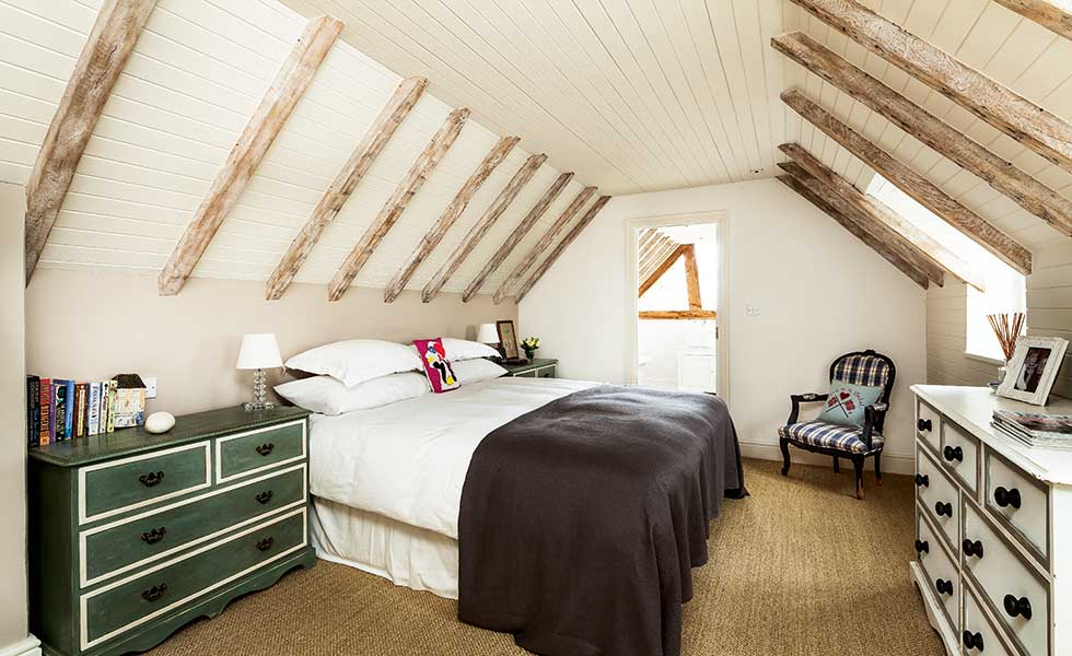 Exposed Rafters And Trusses In A Bedroom With A Vaulted Ceiling