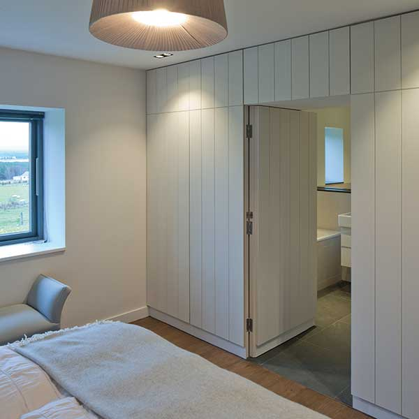 bedroom with cladding walls to bathroom