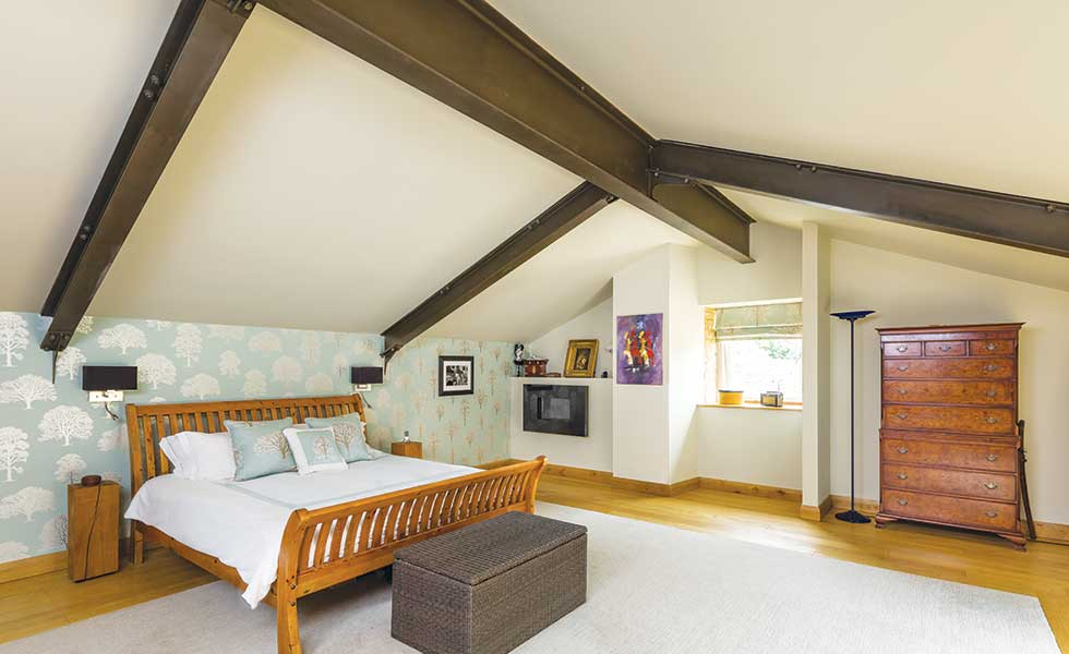 Master bedroom in barn conversion with exposed steel beam