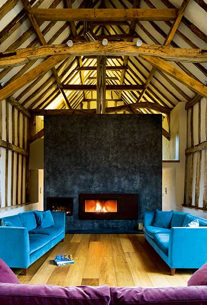 This cosy woodburning stove sits in front of a grand double-height feature partition wall in this barn conversion by Hudson Architects