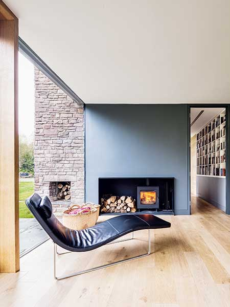 A contemporary fireplace complete with outdoor log store in a new self build home