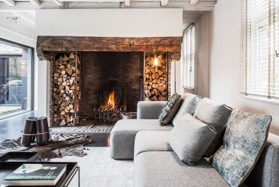 A Scandi-style living room complete with woodburning stove and log store in a Berlin project by JUMA Architects