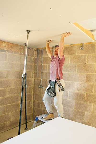 Chris begins tacking the ceilings and walls with studwork in David's self-build and