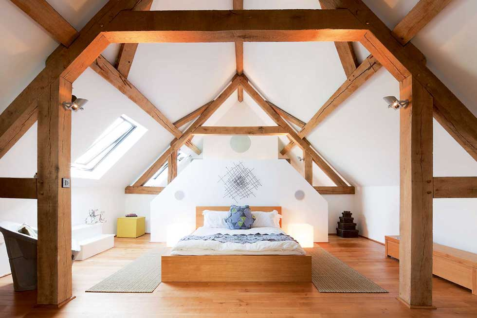 oak frame exposed beams in the bedroom of a barn conversion
