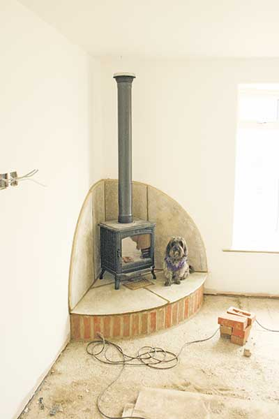 The corner fireplace is built and the woodburning stove installed in David's self build
