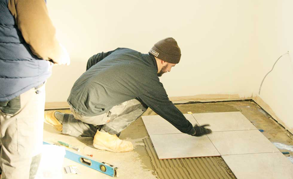 The builders lay the interior floor tiles in David Snell's self build project