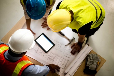 tradesmen look at building plans