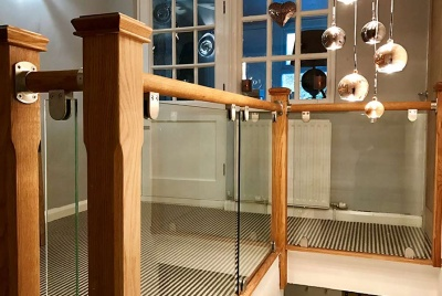 Stairfurb's oak handrail, glass panels & stainless steel brackets create a contemporary landing.