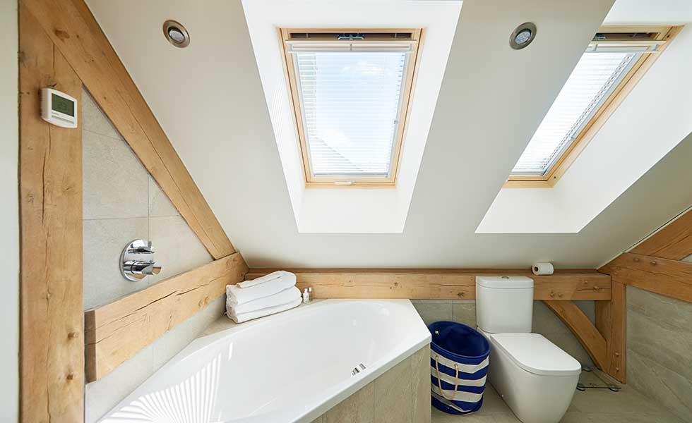 En suite with roof lights and timber beams